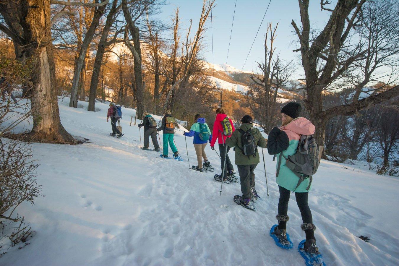personas caminando con raquetas de nieve en el cerro chapelco montaña san martin de los andes